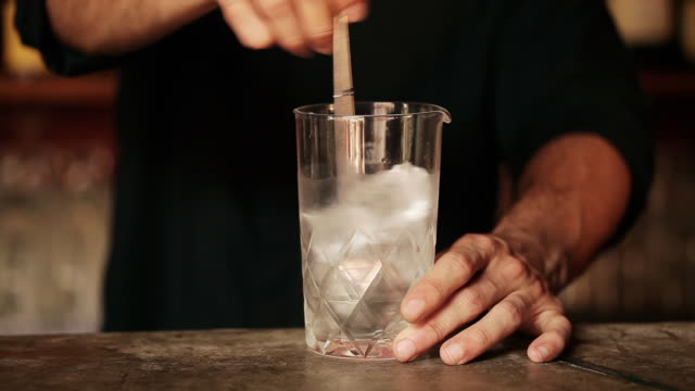 Bartender stirring ice cubes in glass