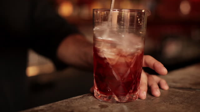 bartender stirring negroni cocktail - mischen stock-videos und b-roll-filmmaterial