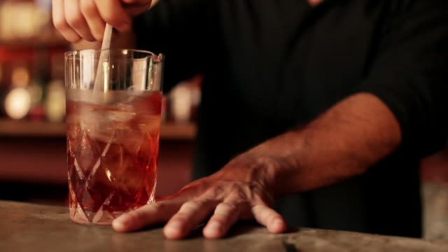 stockvideo's en b-roll-footage met bartender stirring negroni in glass - cocktail