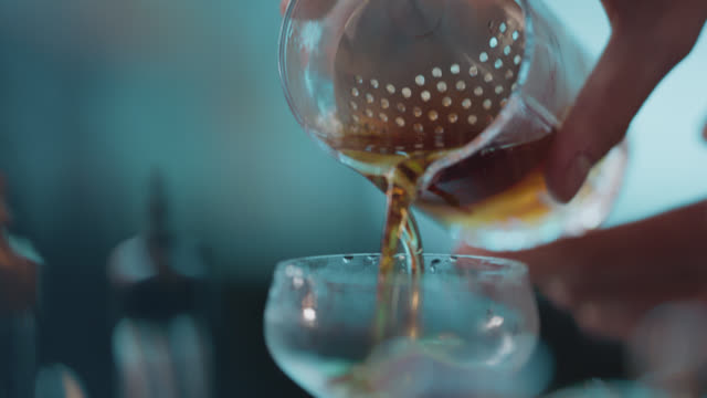slo mo. cu. bartender strains a cocktail while making a drink - nightlife stock videos & royalty-free footage
