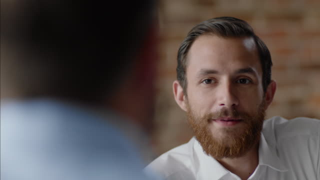 vidéos et rushes de bartender strokes beard and talks with business owner in staff meeting - directeur
