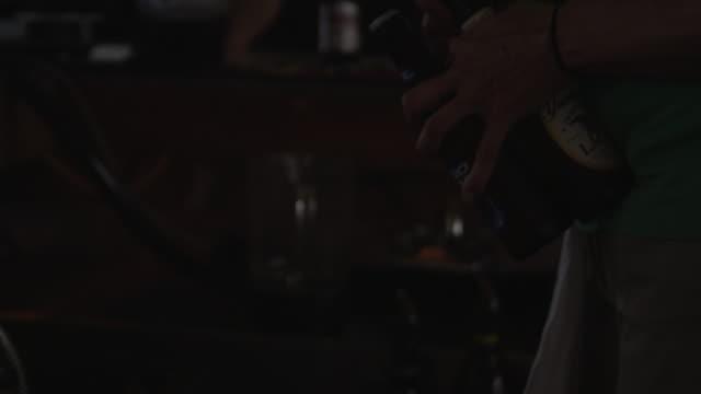 vidéos et rushes de bartender taking caps off two bottles of beer - bouteille de bière