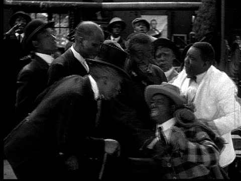 1916 B&W MS bartender throwing small crying man in suit with bags of chickens out of bar/ man pickup up chicken and laughing