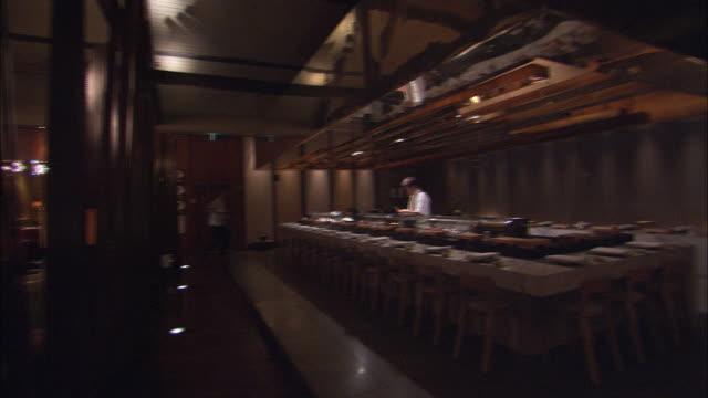 A bartender tidies a bar while a hotel restaurant awaits patrons.