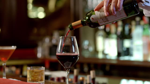 vídeos y material grabado en eventos de stock de bartender topping off glass of red wine from bottle on bar counter in upscale restaurant bar - botella de vino