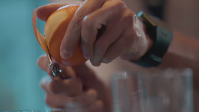 slo mo. cu. bartender users a peeler to peel an orange for cocktails - buccia video stock e b–roll