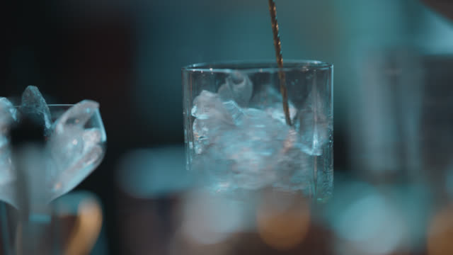 slo mo. cu. bartender uses a long metal stirrer to stir a cocktail while making a drink - alkoholisches getränk stock-videos und b-roll-filmmaterial