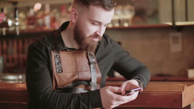 vídeos de stock, filmes e b-roll de bartender usando seu smartphone - misturar