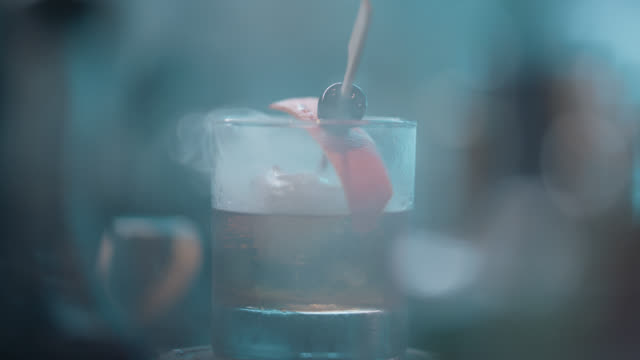 bartender wafts smoke by lifting a glass dome up and down to create a smoky cocktail - bartender stock videos & royalty-free footage