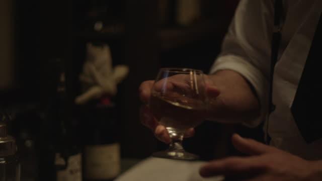 a bartender wearing an apron swirls liquid in a glass brandy snifter. - brandy snifter stock videos and b-roll footage