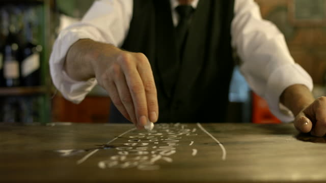 vídeos de stock e filmes b-roll de cu bartender writes with chalk on wooden bar counter in tapas bar - cultura espanhola