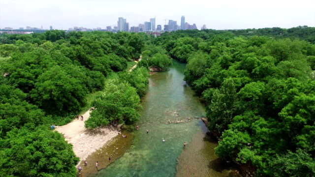barton springs with austin cityscape skyline aerial shot of texas hill country paradise 4k - austin texas stock videos & royalty-free footage