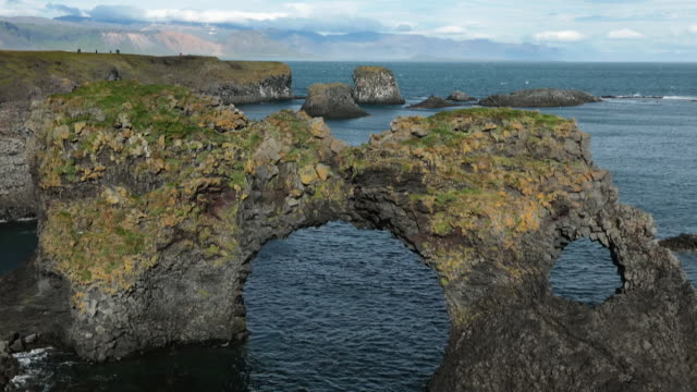 basalt arch on seashore of the atlantic ocean, iceland. - basalt stock videos & royalty-free footage
