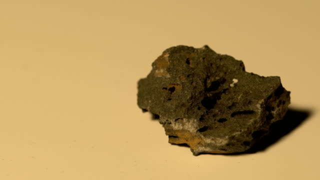 basalt mineral sample in rotation with white background - basalt stock videos & royalty-free footage