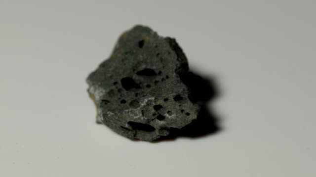 basalt mineral sample in rotation with white background - rock object stock videos & royalty-free footage