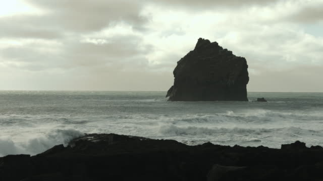 a basalt rock stack stands off the coastline of the reykjanes peninsula in iceland. - basalt stock videos & royalty-free footage