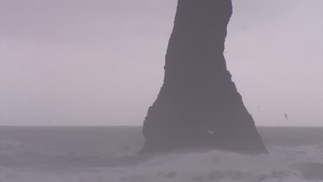 basalt sea stack near the dyrholaey peninsula. - dyrholaey stock videos & royalty-free footage