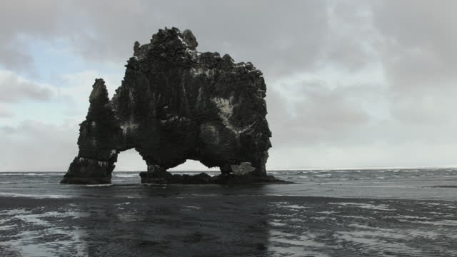 vídeos de stock, filmes e b-roll de a basalt sea stack stands on a beach on the coast of northern iceland. - erodido