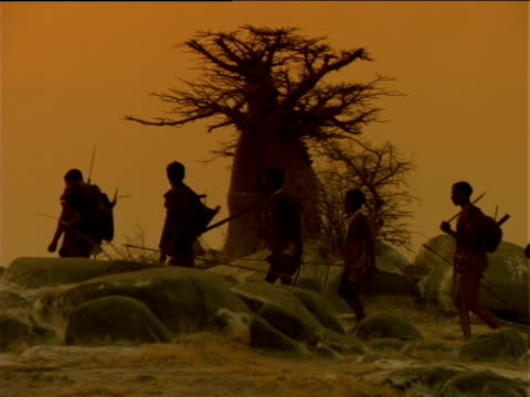 Basarwa tribes people walking along rocky landscape at sunset