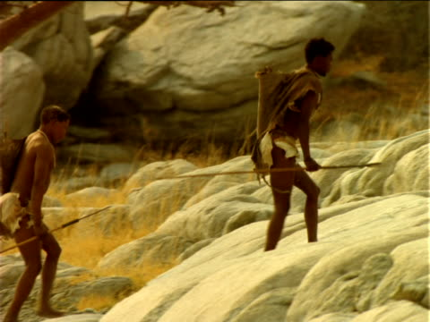 Basarwa tribesmen holding spears walk up rocks, Botswana