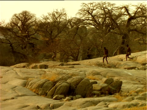 Basarwa tribesmen walk over rock outcrops carrying spears, Botswana