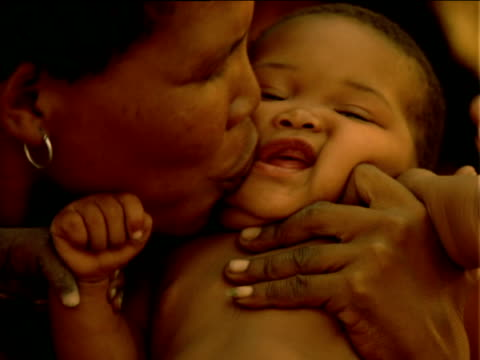 Basarwa tribeswoman affectionately bouncing and kissing her baby