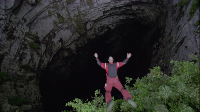 a base jumper falls into the cave of swallows, mexico. available in hd. - höhle stock-videos und b-roll-filmmaterial