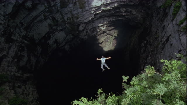 a base jumper free falls in the cave of swallows, mexico. available in hd. - höhle stock-videos und b-roll-filmmaterial