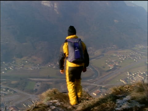 rear view base jumper in yellow suit jumping off cliff / flash frames / europe - stunt person stock videos & royalty-free footage