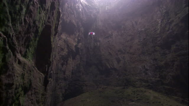 A base jumper parachutes into the Cave of Swallows in Mexico. Available in HD.