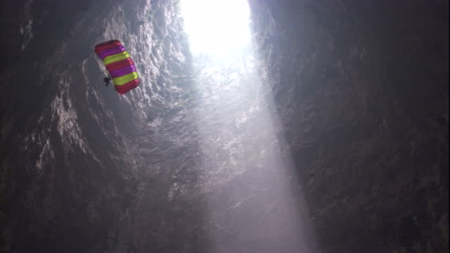 a base jumper parachutes into the cave of swallows through a beam of sunlight. available in hd. - cave stock videos & royalty-free footage