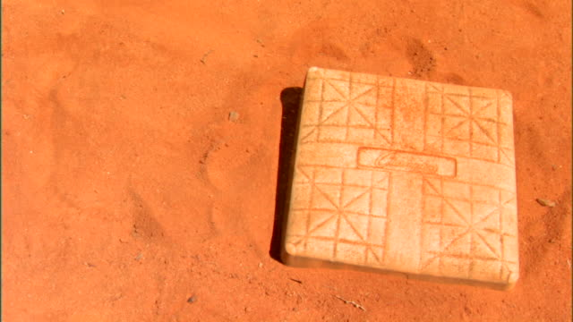 Baseball base marker on clay dirt diamond sand moving over top of base repeats