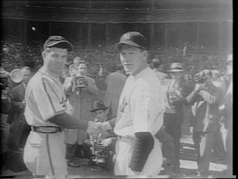 Baseball commissioner KM Landis speaks into BBC microphone / cameras flash at managers William 'Billy' Southworth and Joe McCarthy as they look at...