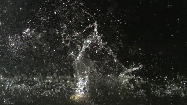 SLO MO, MS,Baseball falling into water against black background
