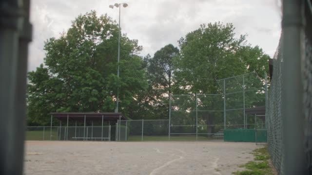 baseball field sits empty under a cloudy sky - baseball diamond stock videos & royalty-free footage