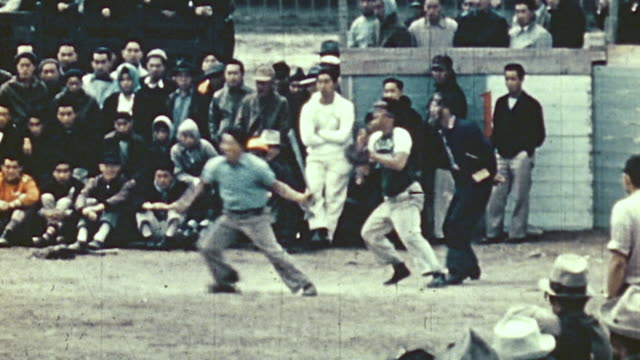 baseball games and touch football games being played before crowds at a world war ii war relocation center for interned citizens / united states - touch football video stock e b–roll