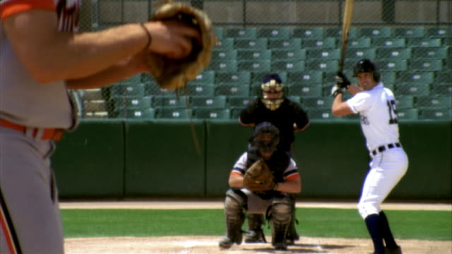 SLO MO MS Baseball pitcher throwing ball, batter, catcher and umpire in home base in stadium / Lancaster, California, USA