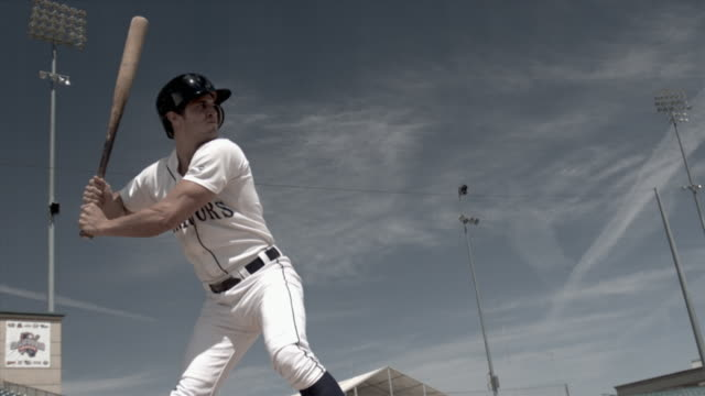 slo mo ms baseball player batting and running toward first base in stadium / lancaster, california, usa - 揺らす点の映像素材/bロール