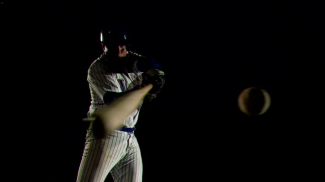 a baseball player hits a ball, knocking dust off the bat. - frivarv bildbanksvideor och videomaterial från bakom kulisserna