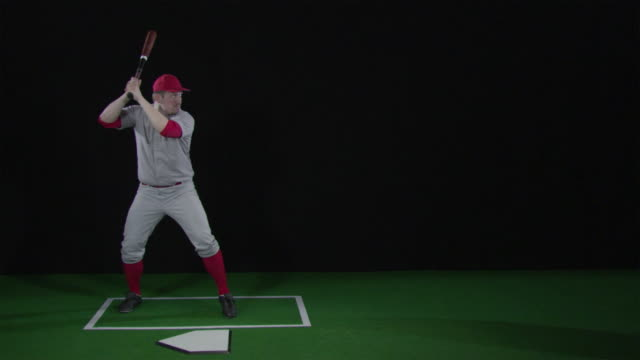 ws slo mo baseball player hitting baseball with bat / berlin, germany - 揺らす点の映像素材/bロール