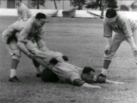 vídeos y material grabado en eventos de stock de b/w 1938 baseball player holding second player by legs rolling him on his stomach over ball - uniforme de béisbol