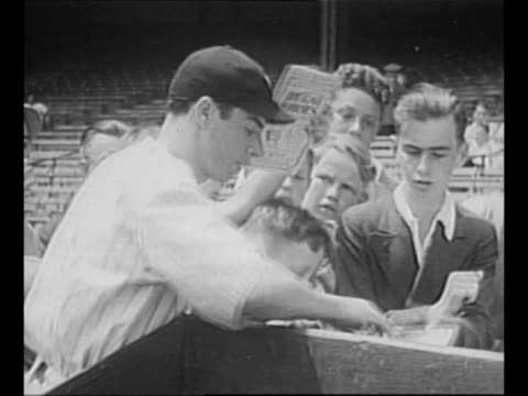 Baseball player Joe DiMaggio walks through crowd of young admirers as he arrives at Yankee Stadium / WS stadium with players on field and packed...