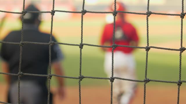 a baseball player makes a play at a game seen through netting. - baseballmannschaft stock-videos und b-roll-filmmaterial