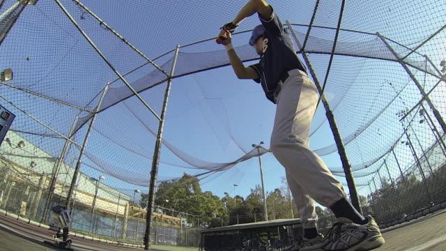 a baseball player practicing at the batting cages. - slow motion - gabbia di battuta video stock e b–roll