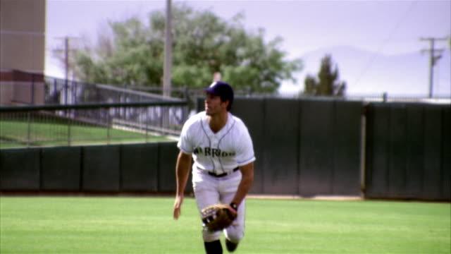 slo mo ms baseball player running and falling on field / lancaster, california, usa - 野球用グローブ点の映像素材/bロール