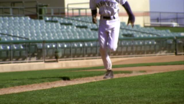 SLO MO CU PAN Baseball player running and sliding into base / Lancaster, California, USA