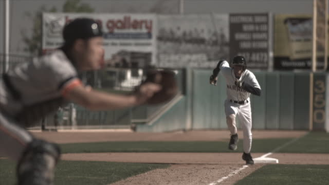 SLO MO WS Baseball player running toward home plate as catcher waits for ball / Lancaster, California, USA