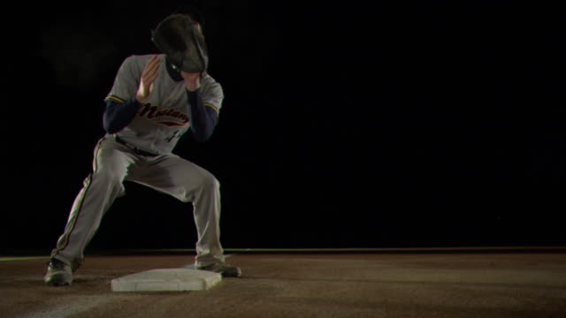 A baseball player slides into third base.