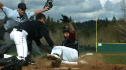 Baseball player slides is safe at home plate, slow motion