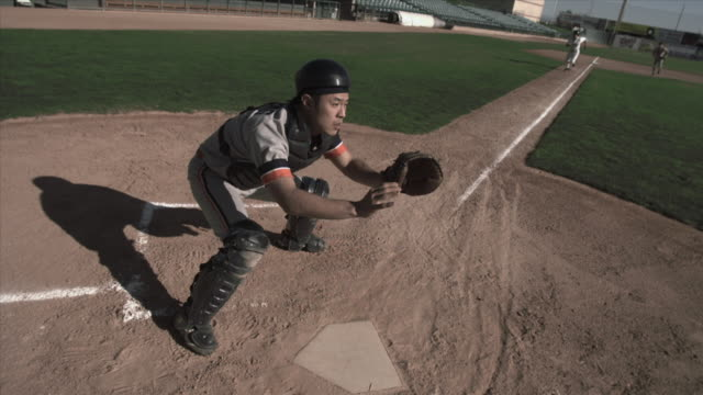 slo mo ha ws baseball player sliding into home plate as catcher catches ball and tags him / lancaster, california, usa - 野球点の映像素材/bロール